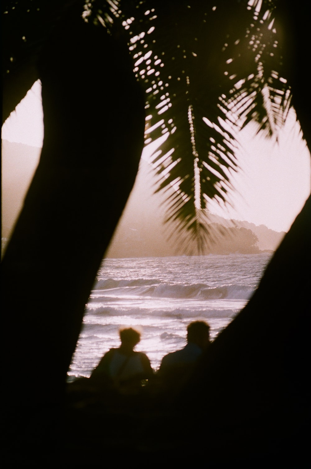 silhouette of 2 person sitting on rock near body of water during daytime