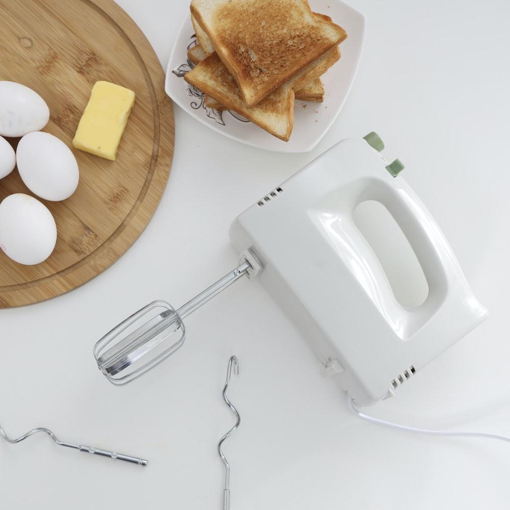 white apple earpods beside bread on white ceramic plate