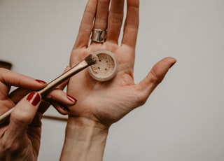 person holding silver round analog watch