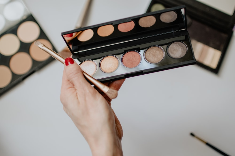 person holding makeup brush with makeup palette