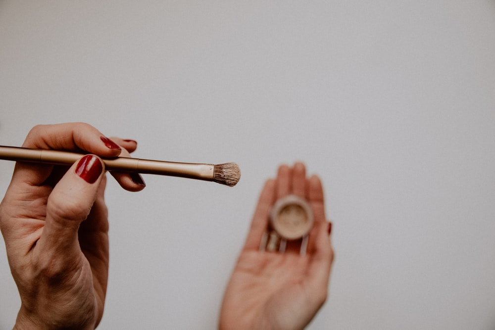 person holding brown and white makeup brush
