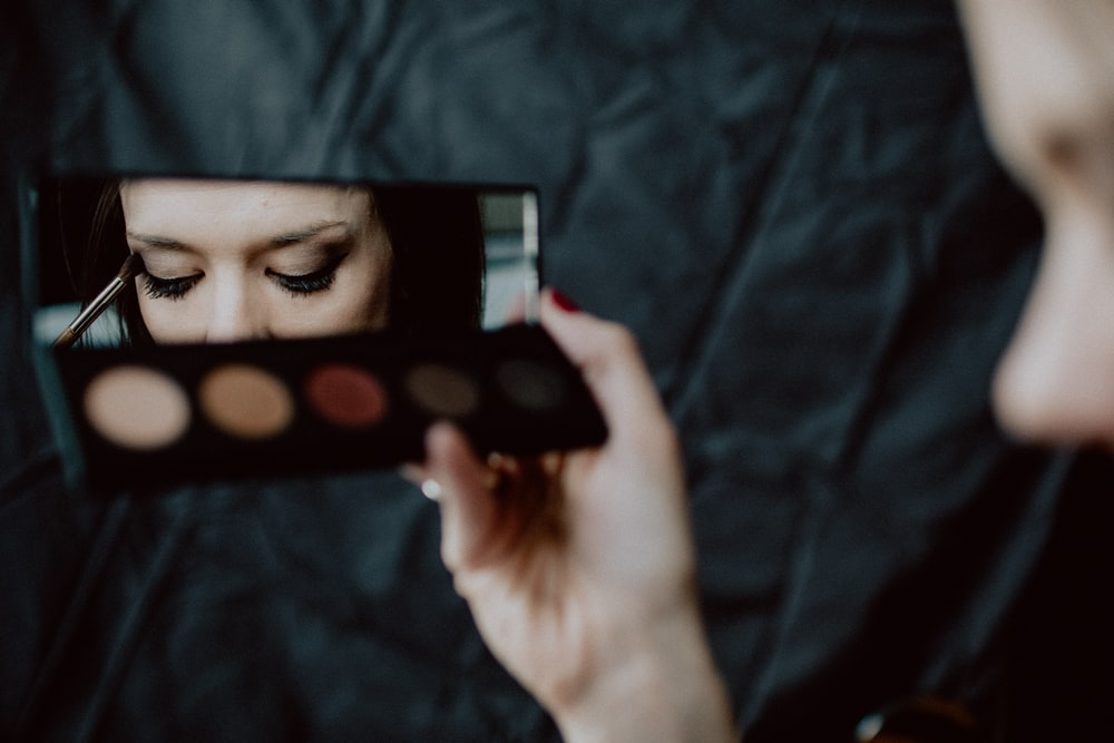 woman holding black and silver make up palette