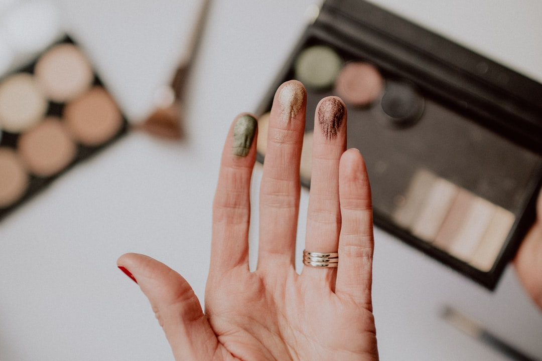 Different colors of eyeshadow testing on a woman's fingertips