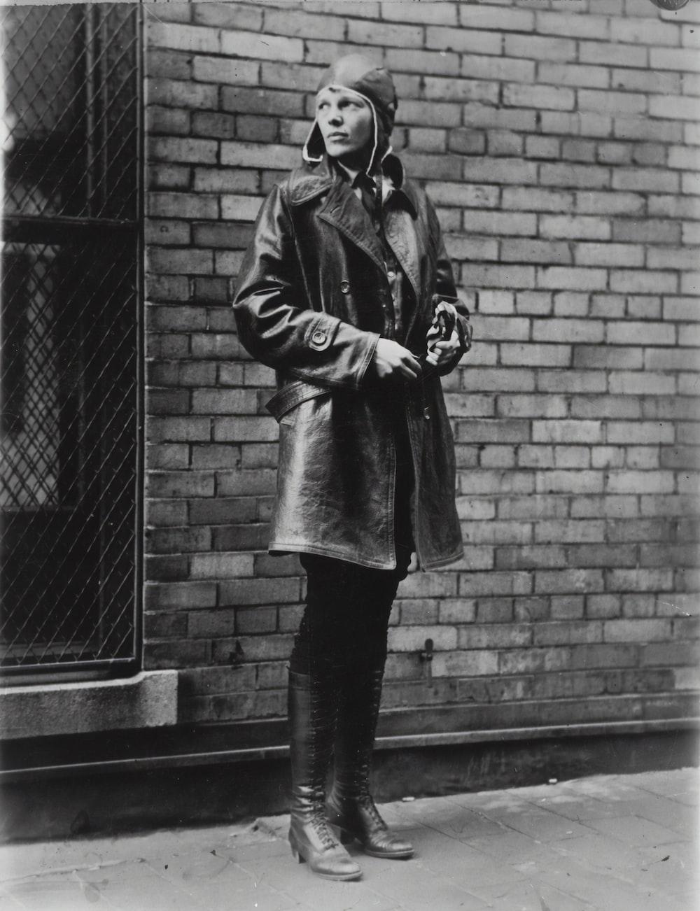 woman in coat standing beside brick wall