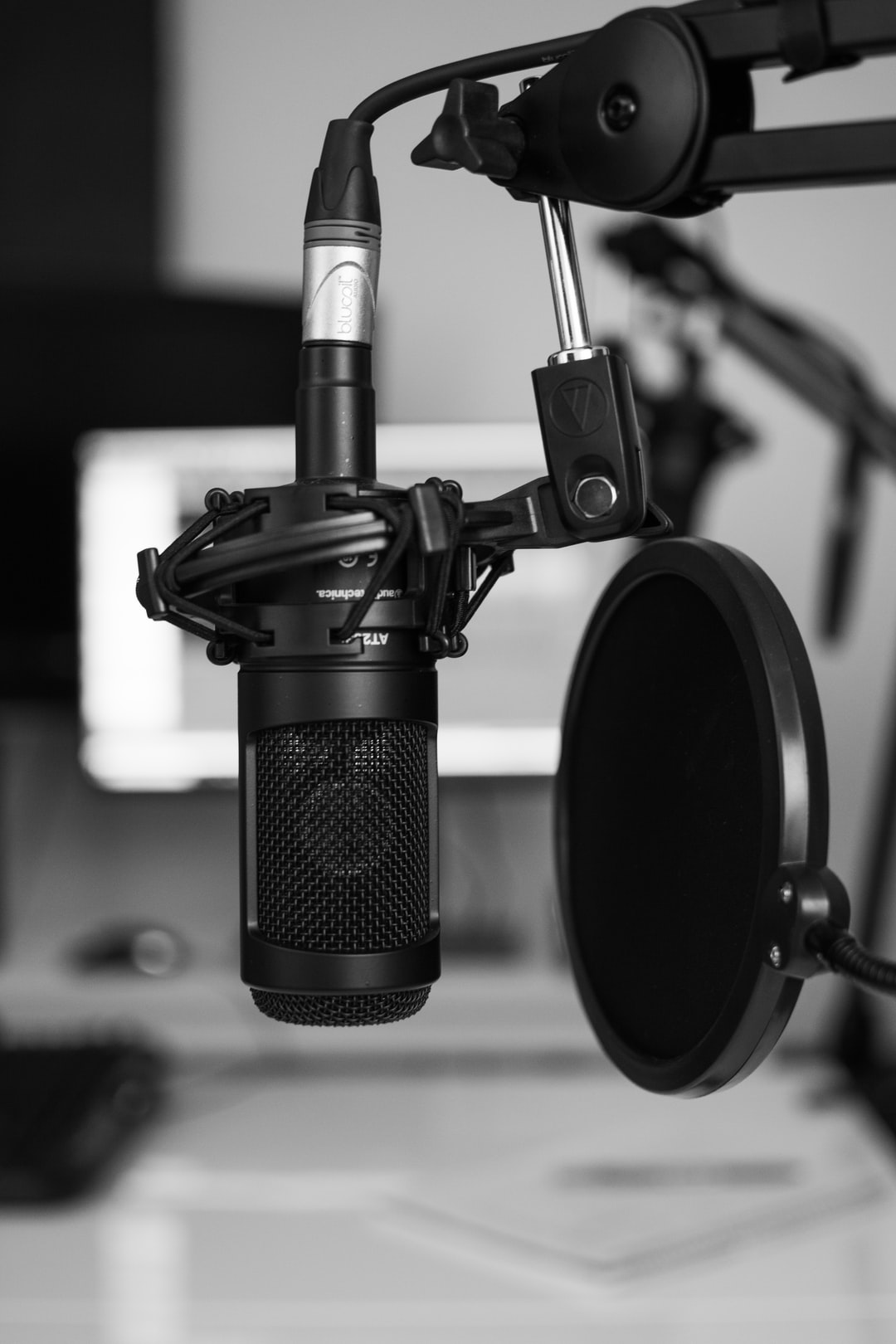 A podcasting microphone with pop filter in black and white.