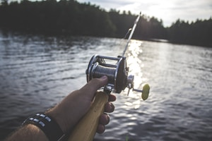person holding black and silver fishing reel