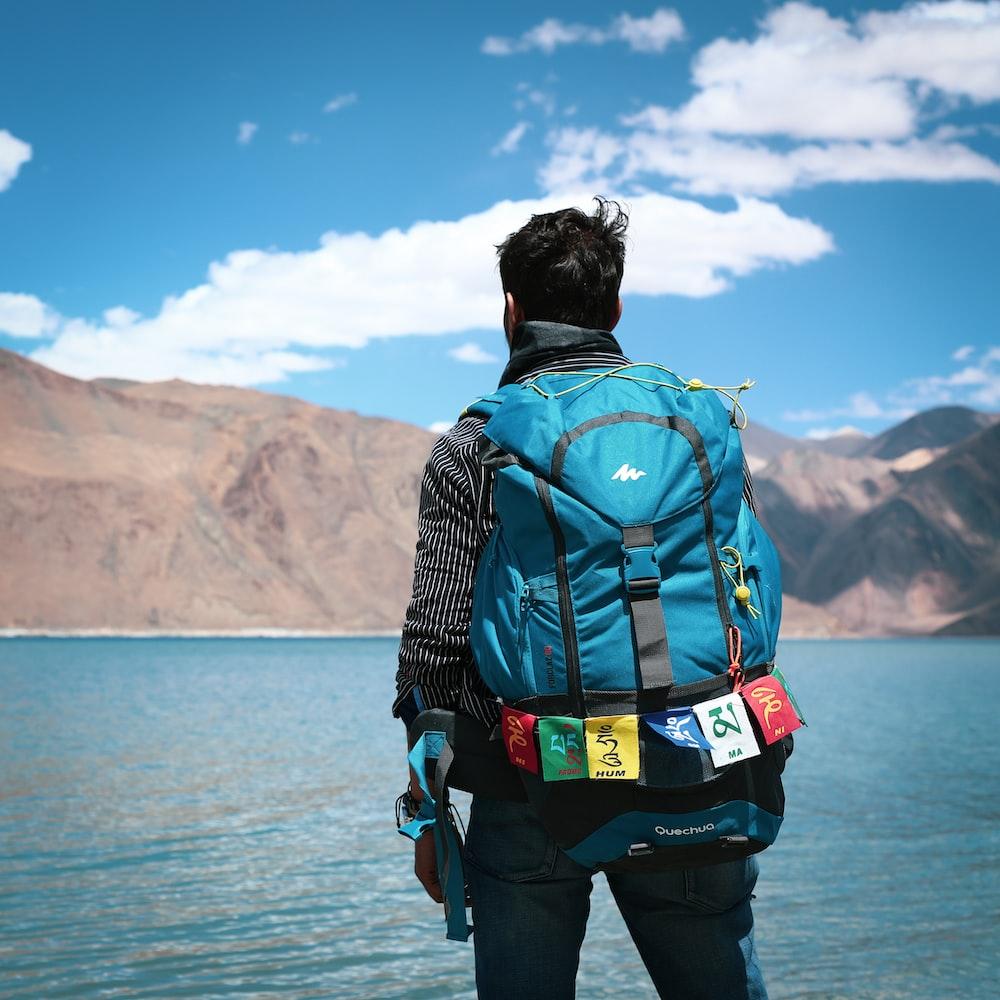 man in blue denim jacket and blue denim jeans with black backpack standing on rock near near near near near