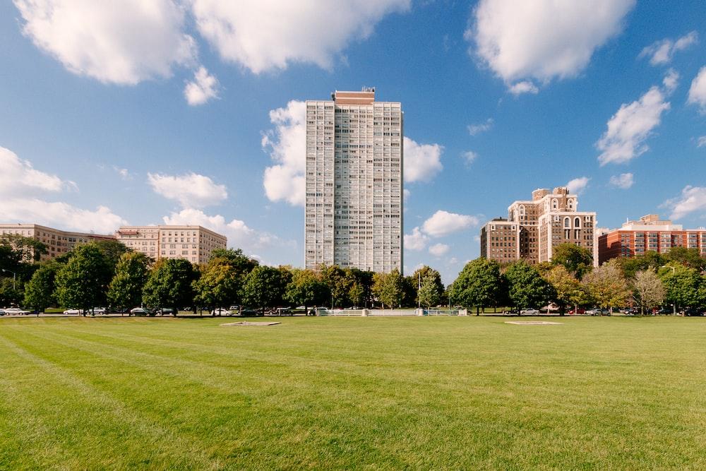 green grass field near city buildings under blue sky during daytime