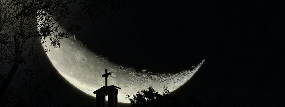silhouette of cross under starry night