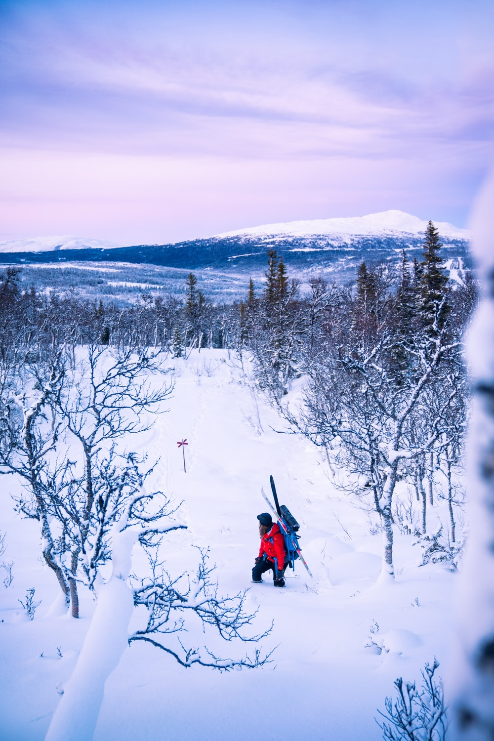 person in red jacket and black pants riding red snow sled on snow covered ground during