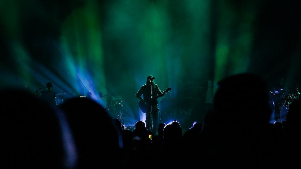 man in black shirt playing guitar on stage