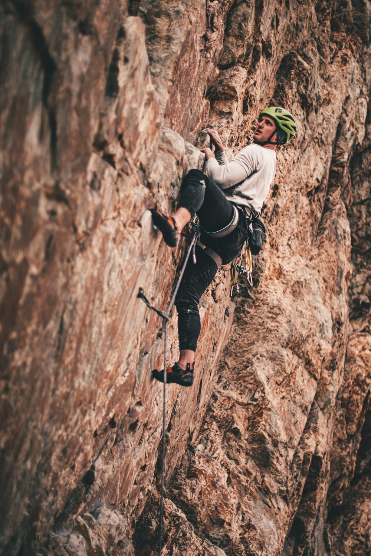 man in black jacket climbing on brown rock mountain during daytime