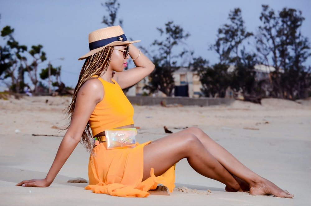 woman in yellow dress sitting on sand during daytime