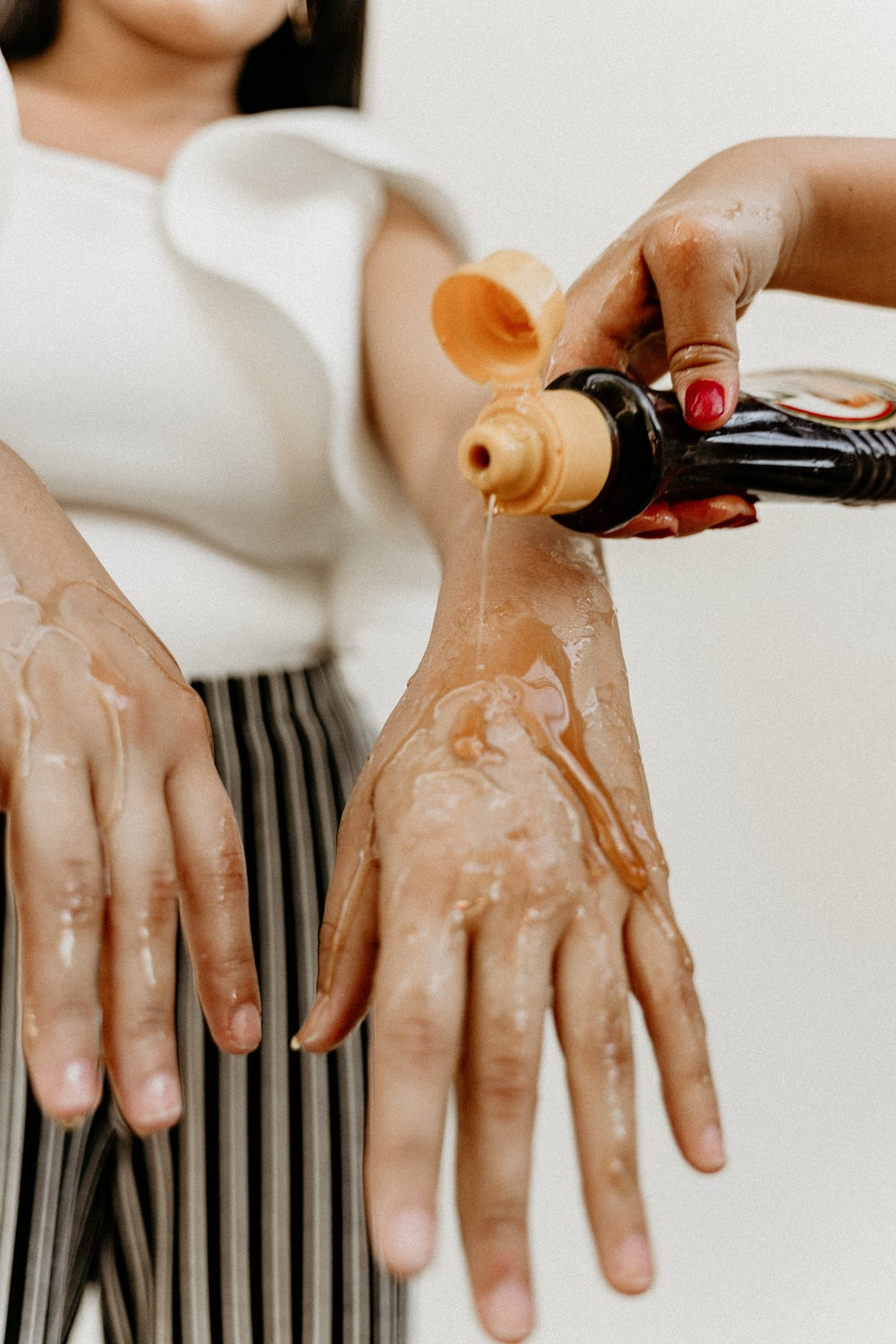 person pouring brown liquid on womans hand