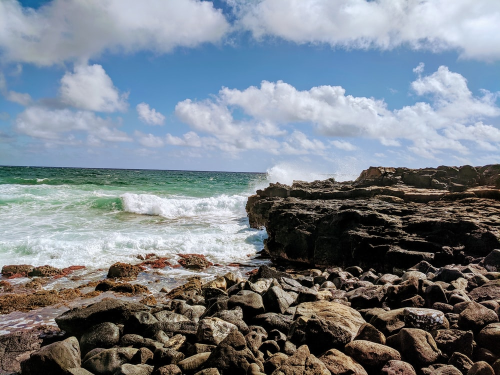 rocky shore under blue sky and white clouds during daytime