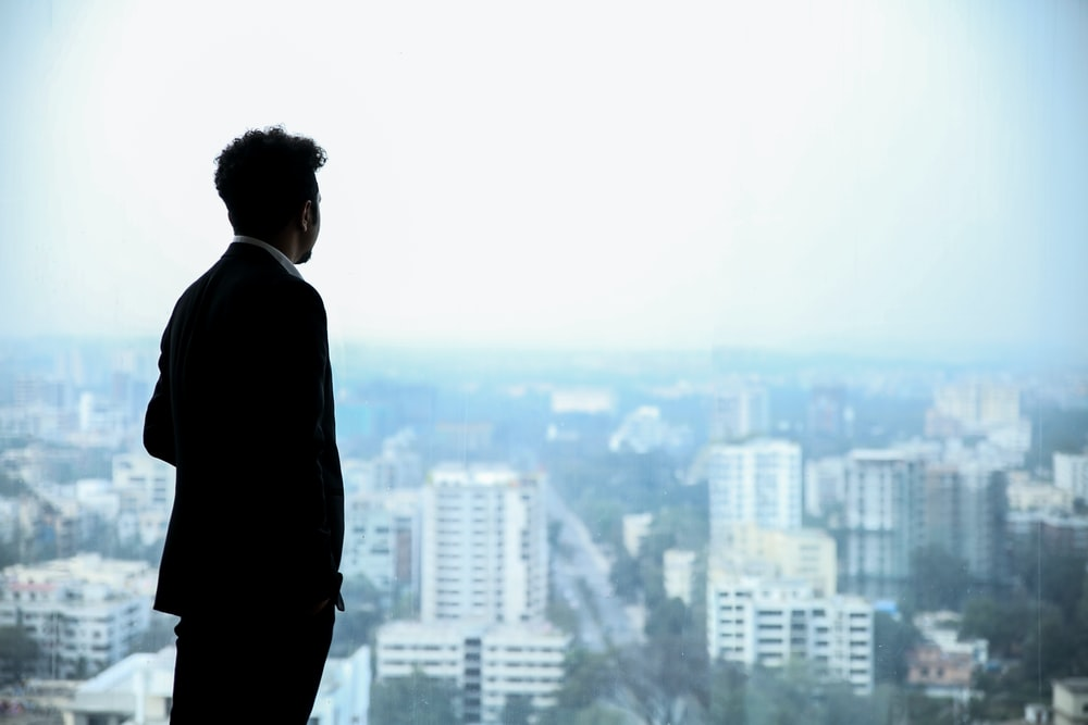 man in black suit standing on top of building looking at city buildings during daytime