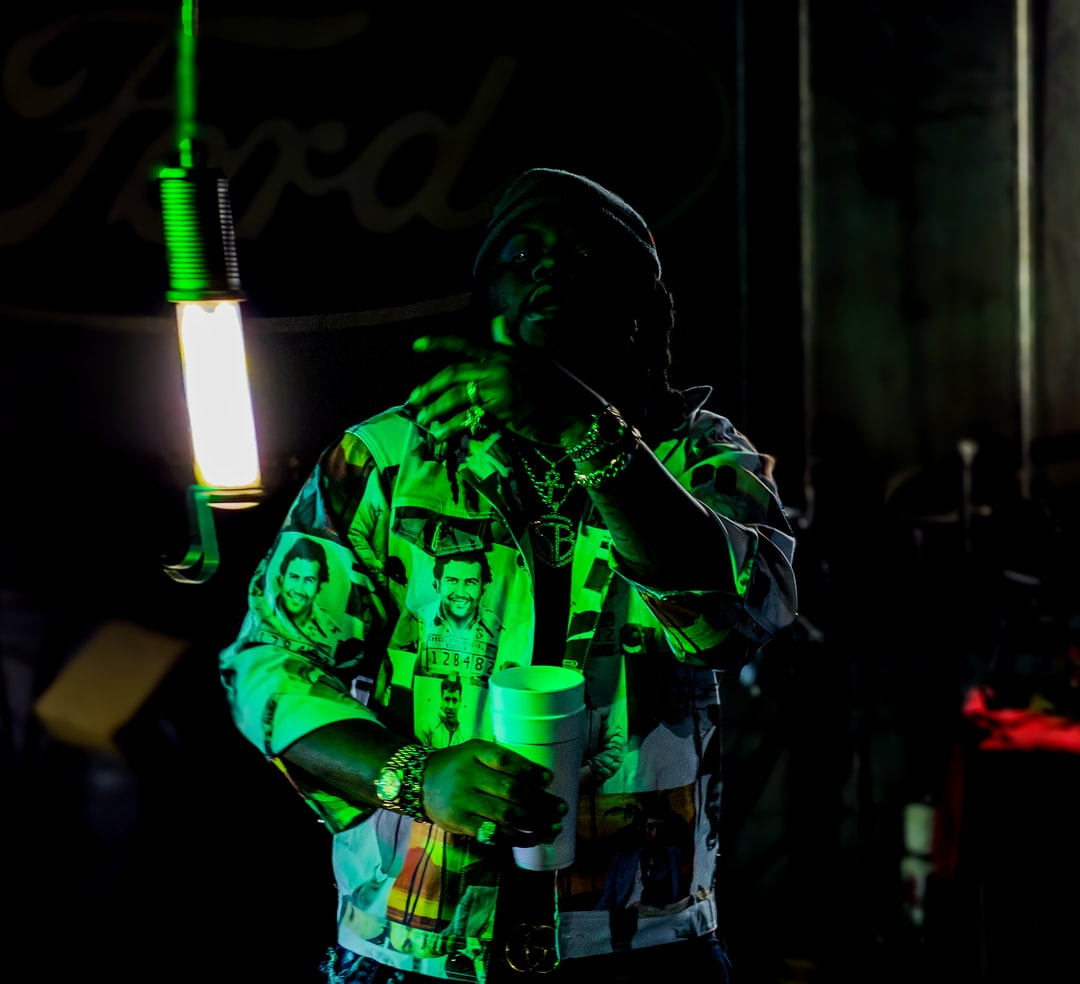 A music artist bathed in neon green light and wearing a jacket depicting dead Narcos, shoots a music video inside of a car repair shop.
