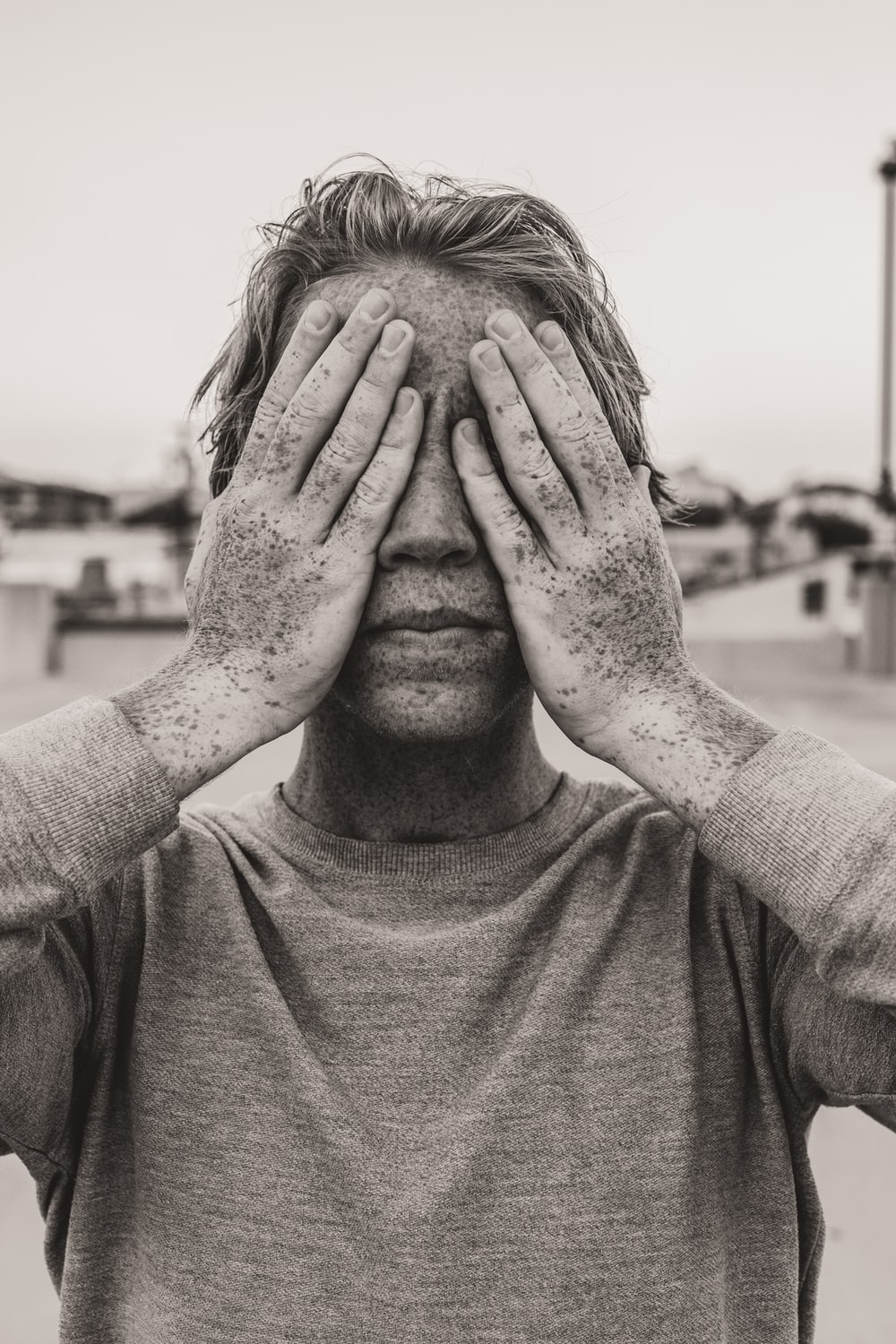 man in gray crew neck shirt covering his face with his hands