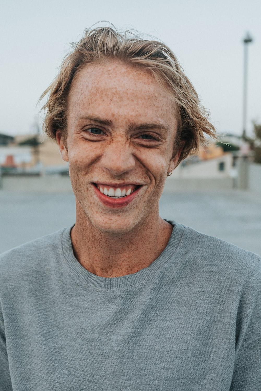 man in gray crew neck shirt smiling
