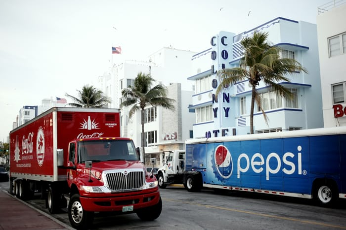 A Cocacola truck next to a Pepsi truck; red color a part of both brands
