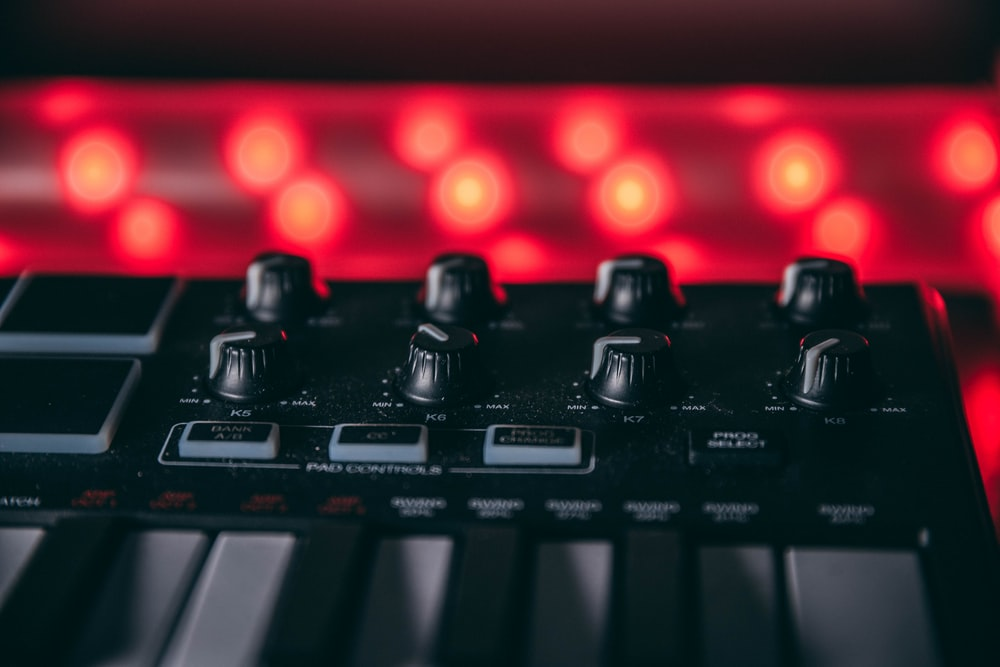 black audio mixer turned on with red lights
