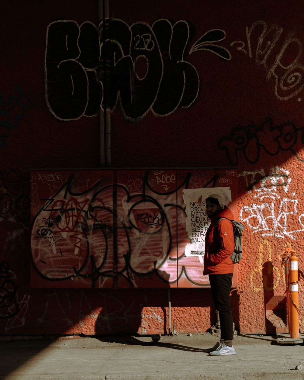 woman in red jacket standing in front of graffiti wall