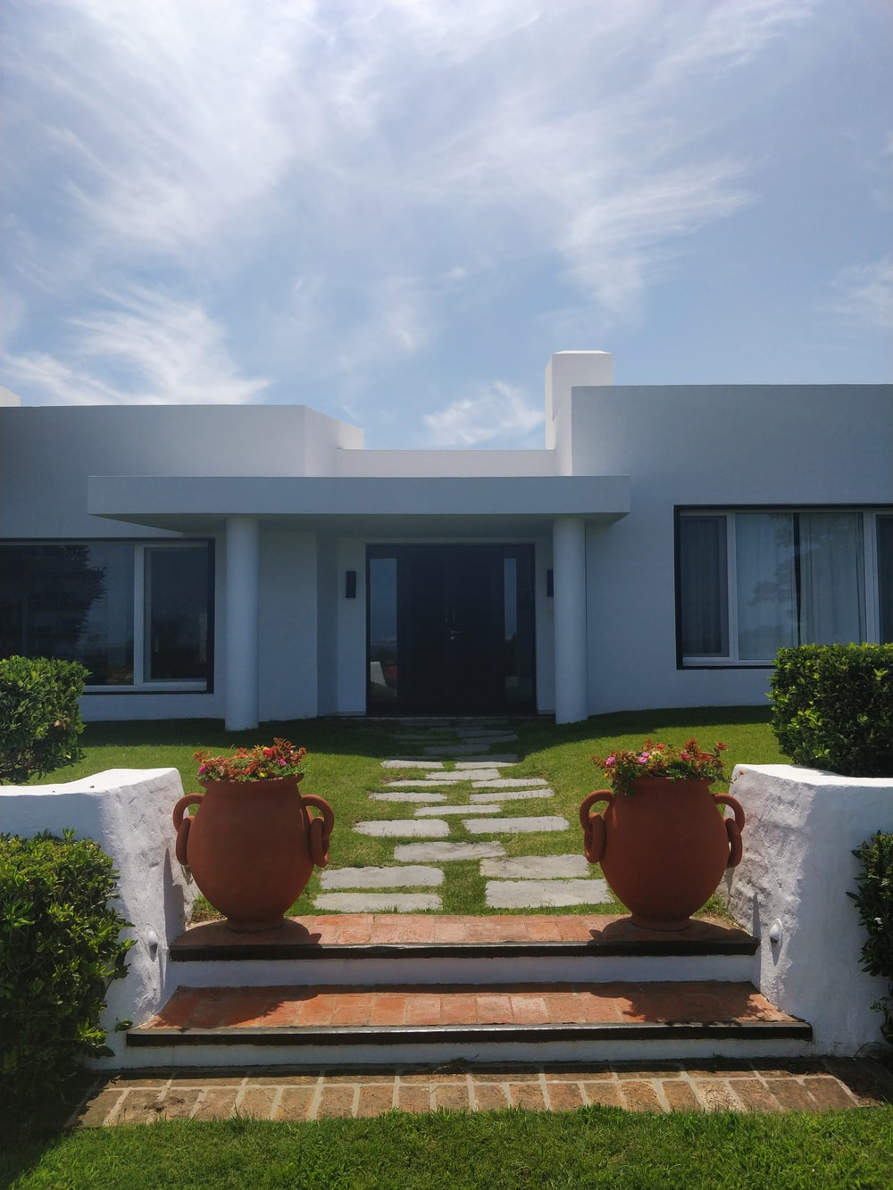 white concrete house under white clouds during daytime
