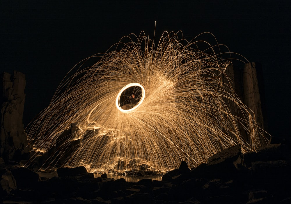 steel wool photography of person standing on brown sand during nighttime