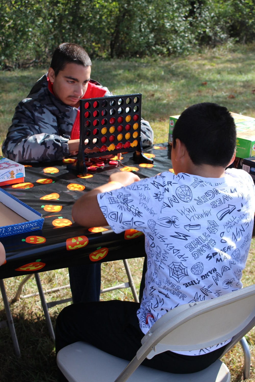 boy in red and black hoodie playing chess