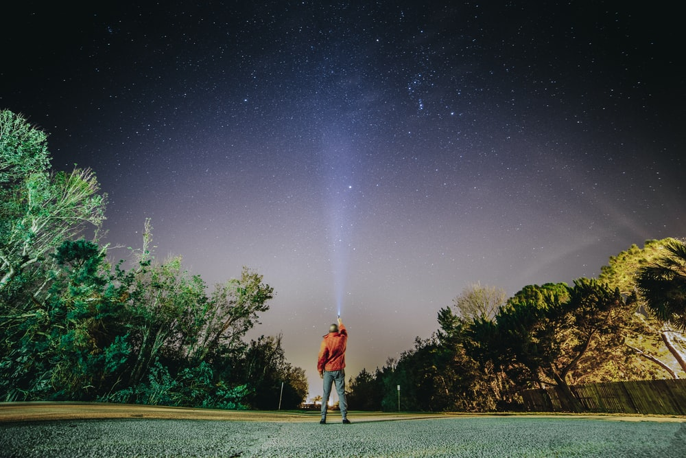 man in red shirt standing on gray concrete pathway under starry night