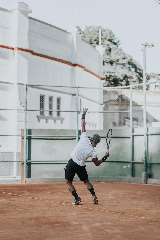 man in white t-shirt playing basketball during daytime