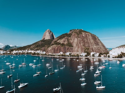 boats on sea near brown mountain under blue sky during daytime rio de janeiro zoom background