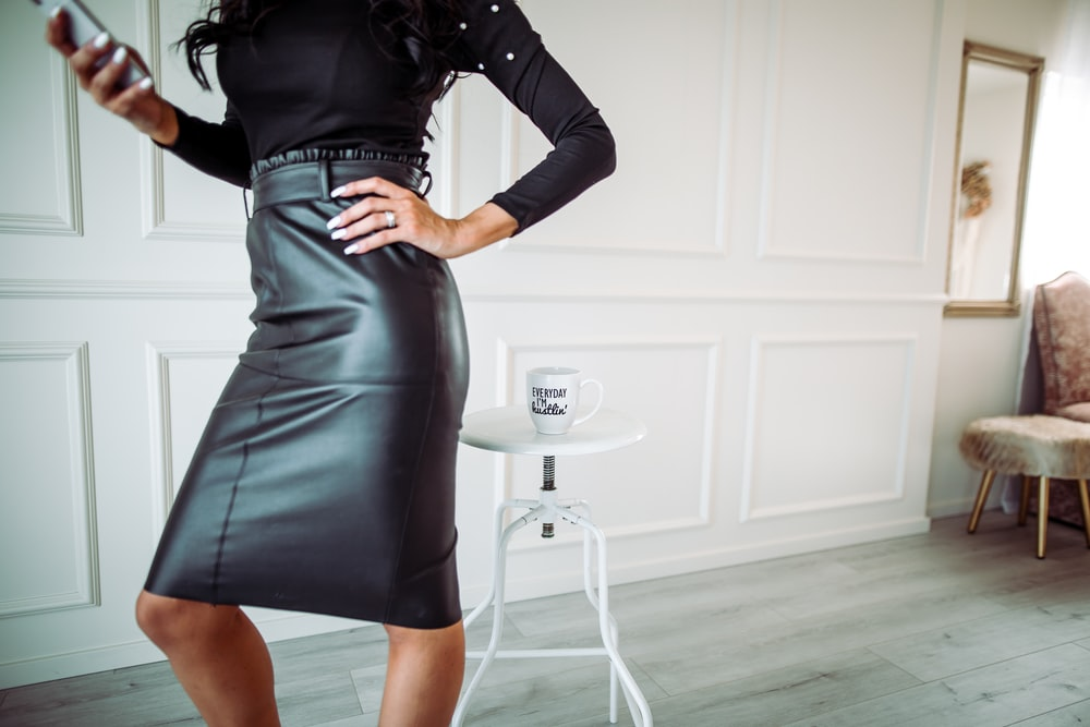 woman in black leather long sleeve dress standing near white wall