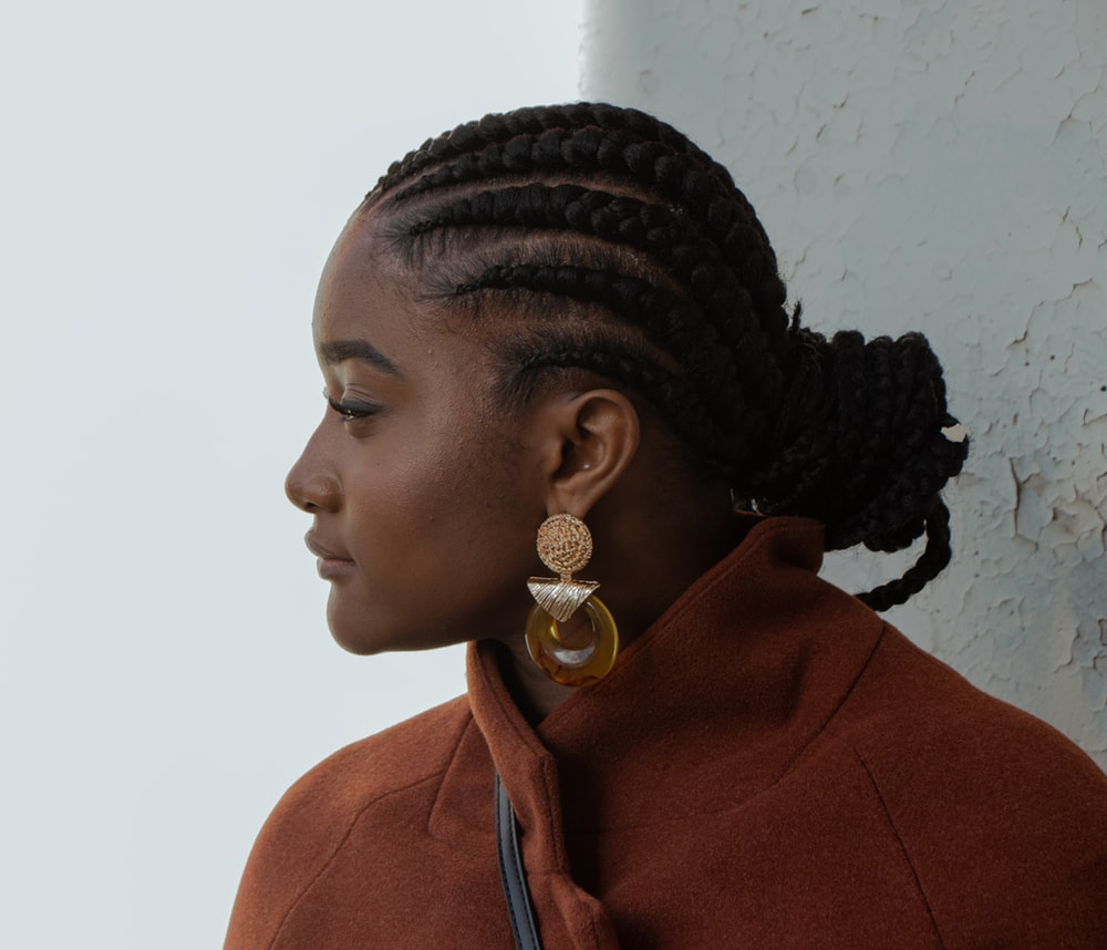 woman in brown coat wearing gold earrings
