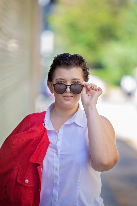 woman in red button up vest wearing black framed eyeglasses