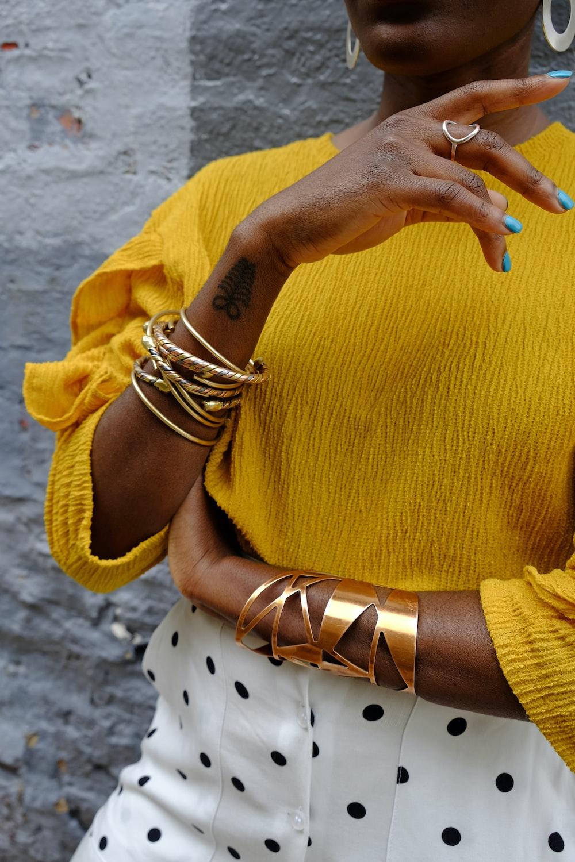 woman in yellow sweater wearing gold bracelet