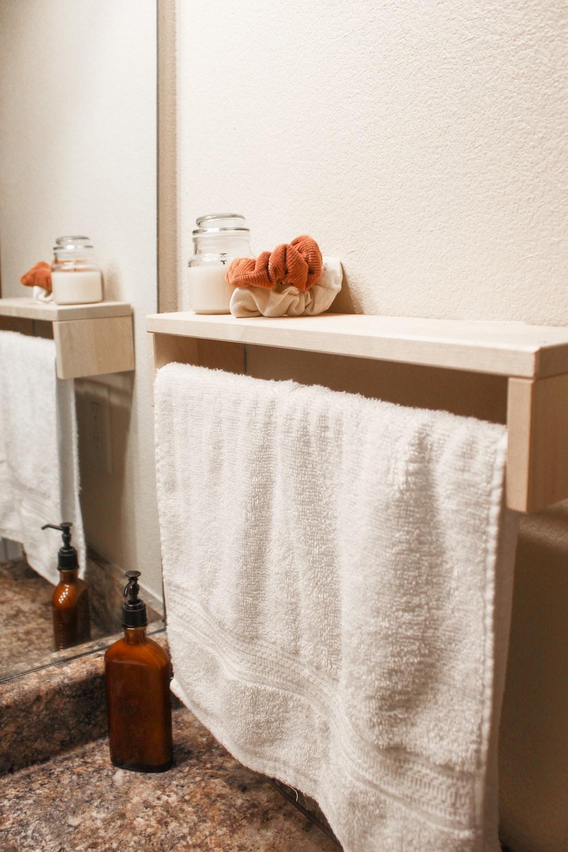 white bath towel on white wooden shelf
