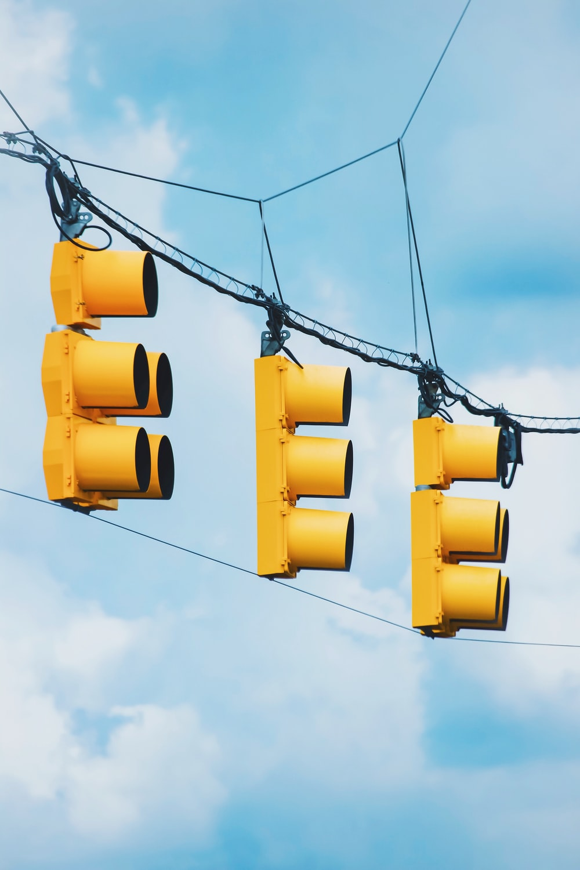 yellow traffic light under blue sky during daytime
