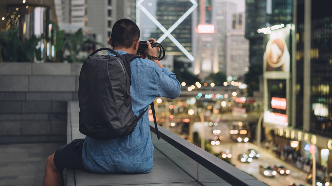 Man wearing an Able Carry backpack taking a photo of Hong Kong at sunset