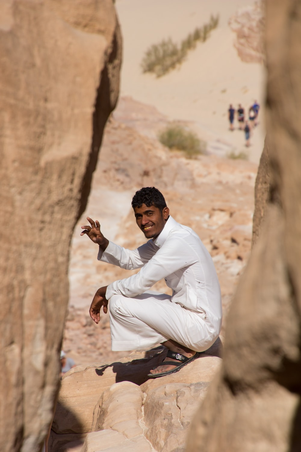 man in white dress shirt and gray pants sitting on brown rock during daytime