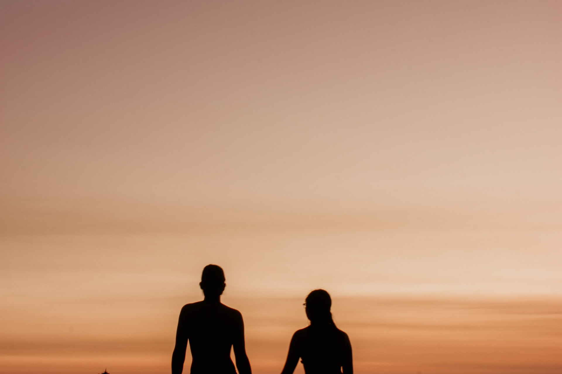 silhouette of 2 men and woman standing on seashore during sunset