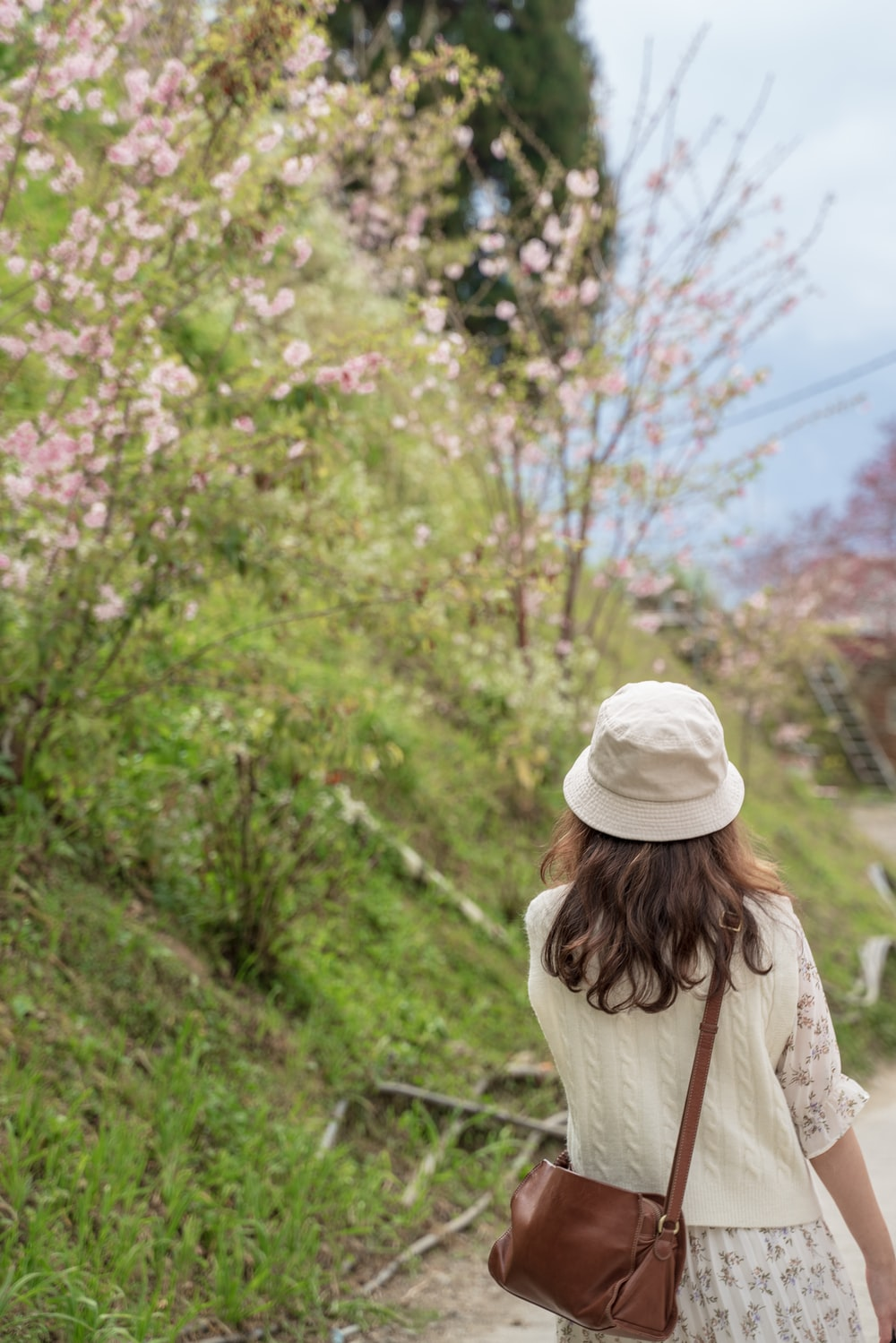 woman in white knit cap standing near green trees during daytime