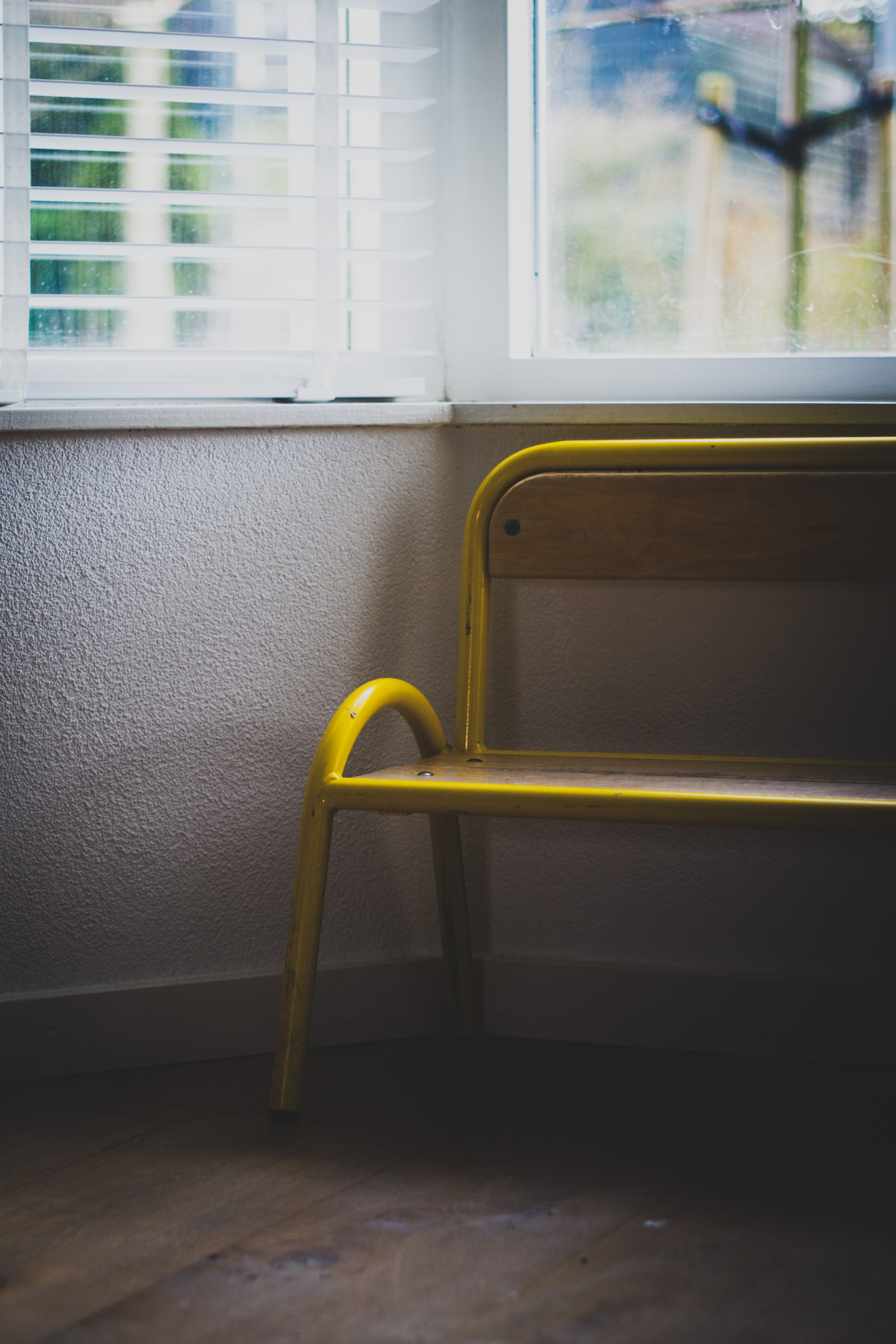 Moody image of a yellow kid chair in the living room