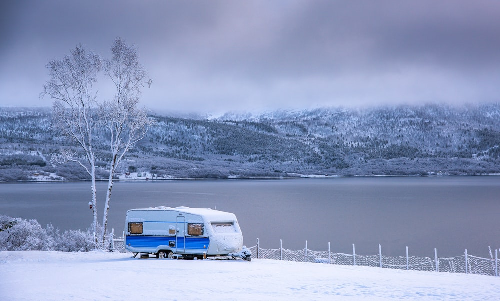 white and brown van on snow covered ground during daytime