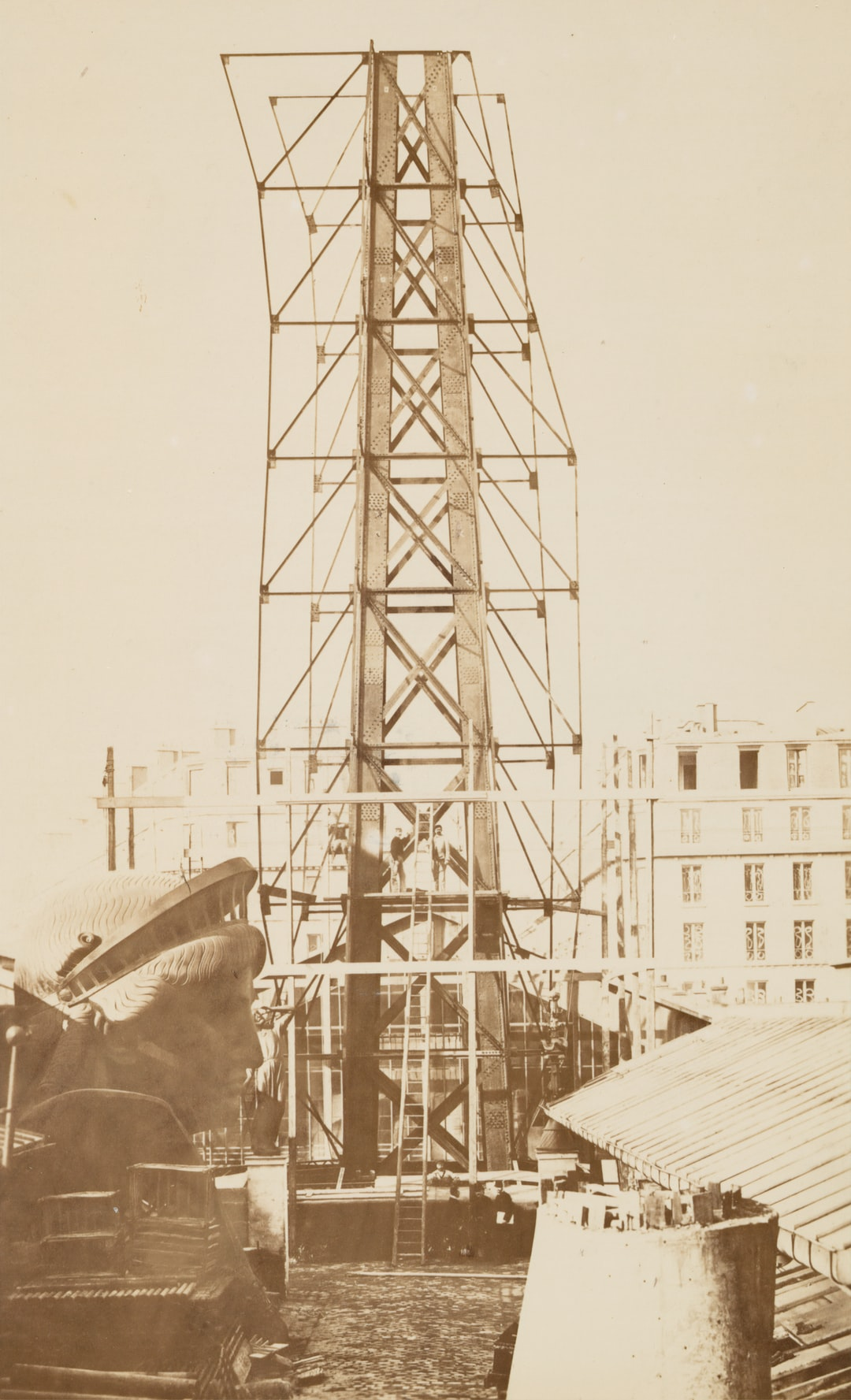 Scaffolding for the assemblage of the Statue of Liberty, of which the head is shown at left, in Paris. 1883