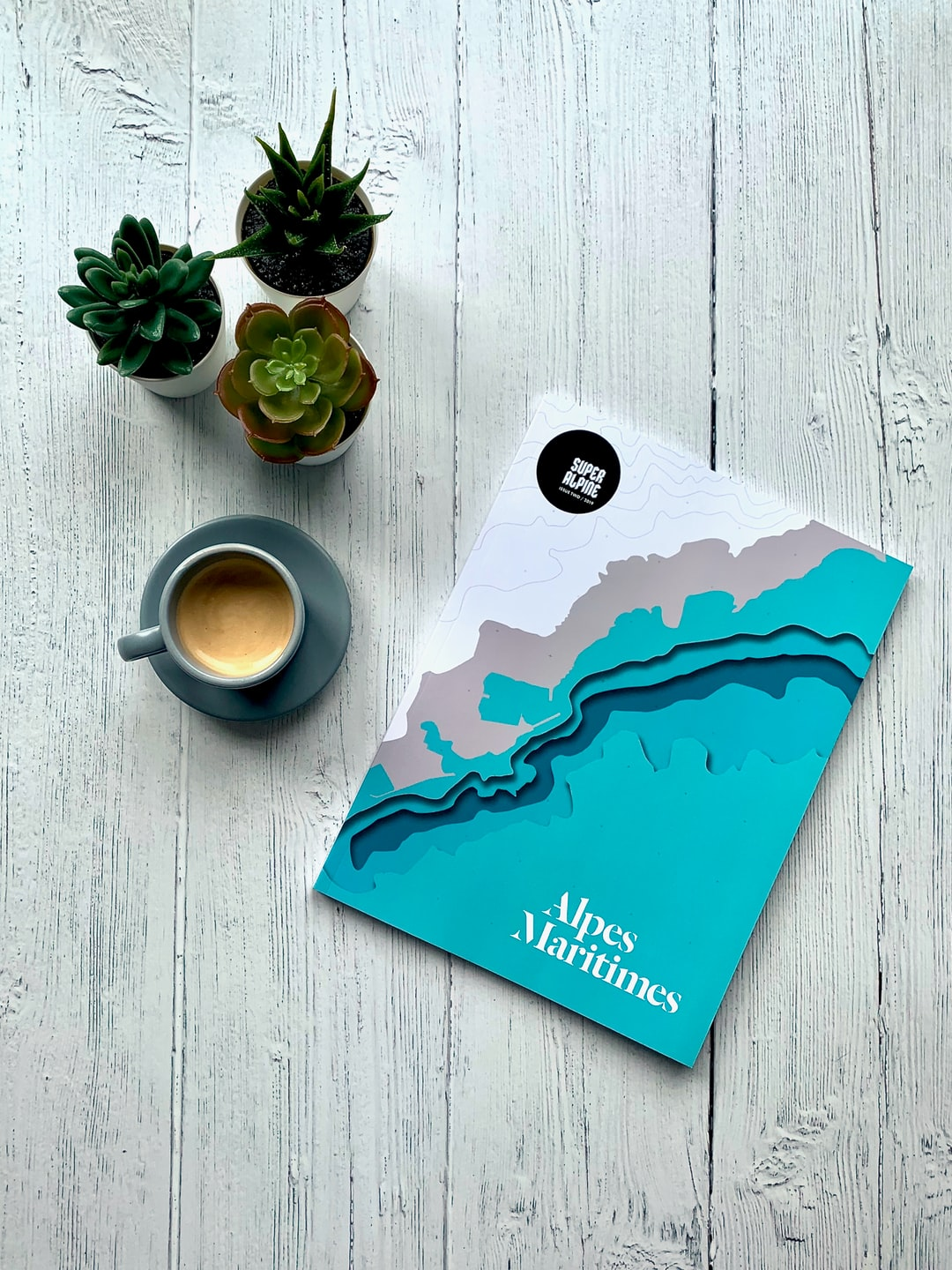 Alpes-Maritimes magazine with an espresso and plants on a wood background