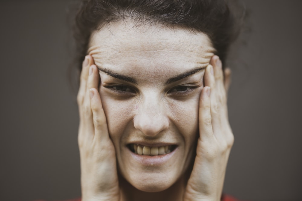 woman in red shirt holding her face