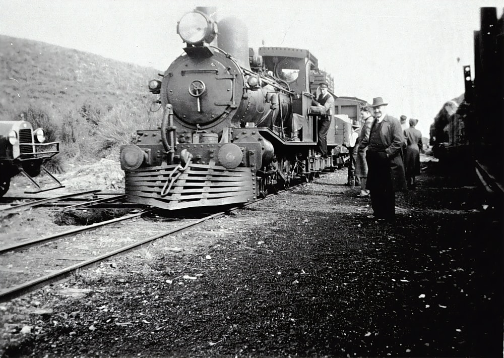 grayscale photo of people standing beside train