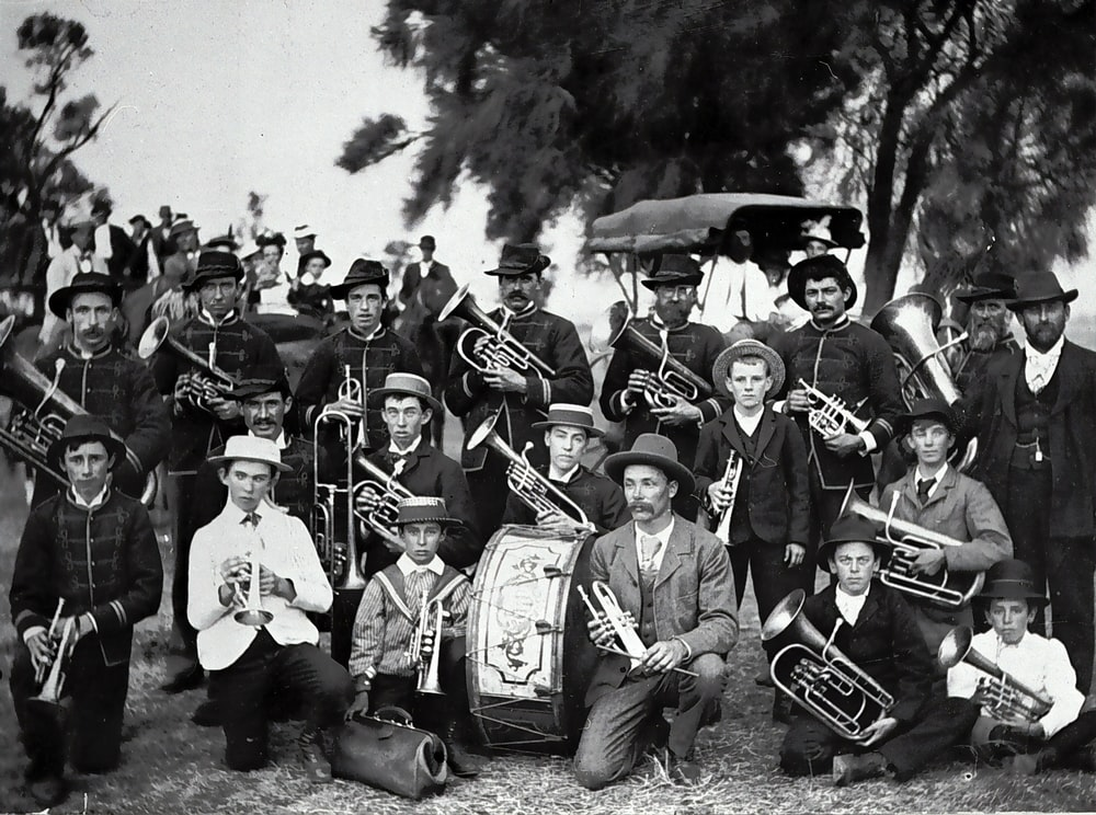 grayscale photo of men in black hat playing musical instrument
