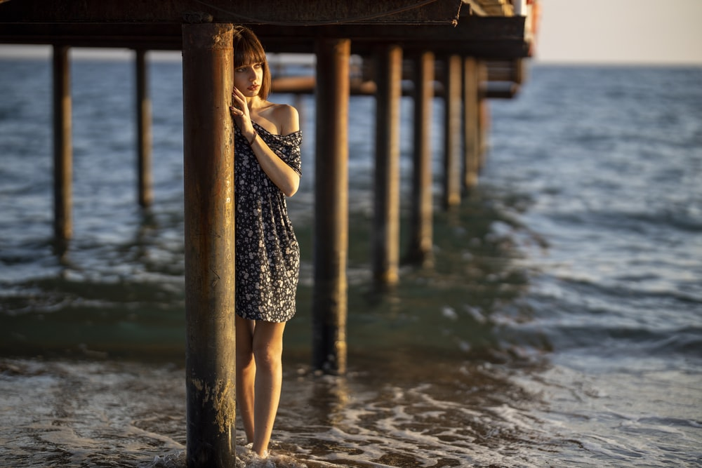 woman in black and white dress standing on wooden dock during daytime